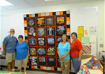 People smiling in front of quilt
