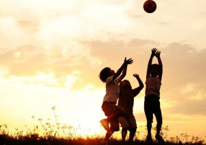kids playing with a ball at sunset