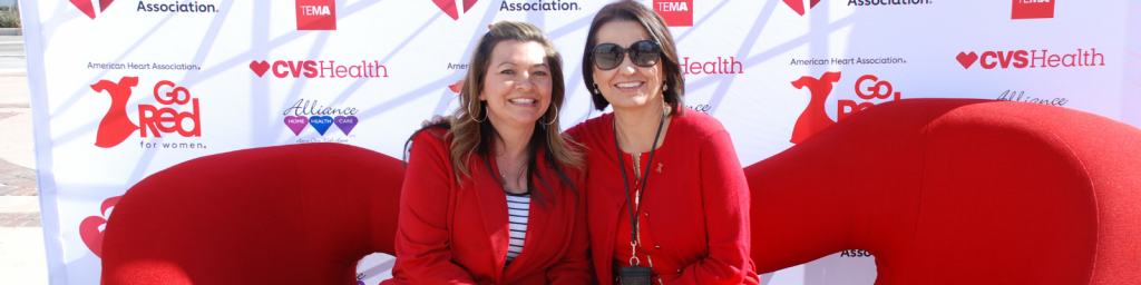 Two women both wearing red sit next to each other on a red couch at an event for the American Heart Association