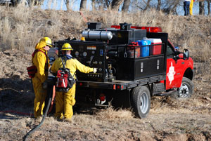 Firefighters putting out a fire by the bosque