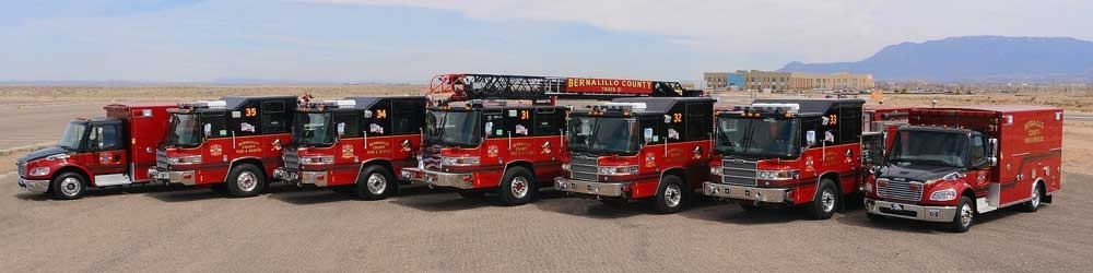 A picture of 7 fire trucks lined up