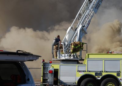 A picture of firefighters and a plume of smoke