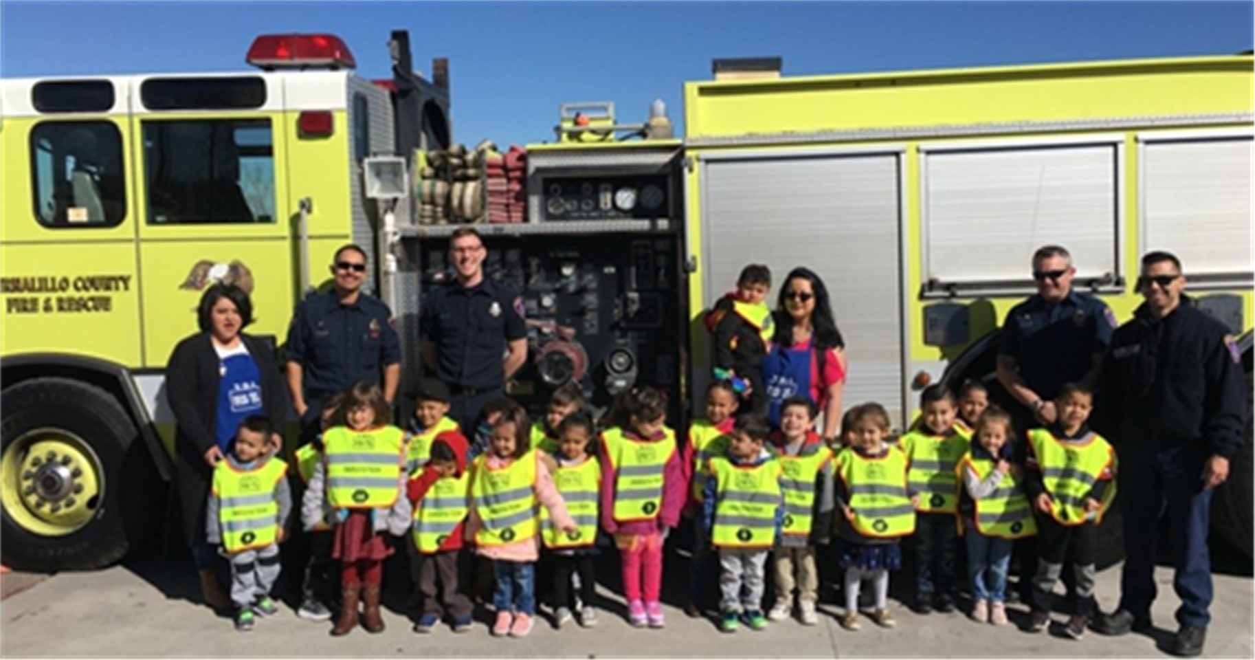 A picture of kids and firemen in front of a fire truck