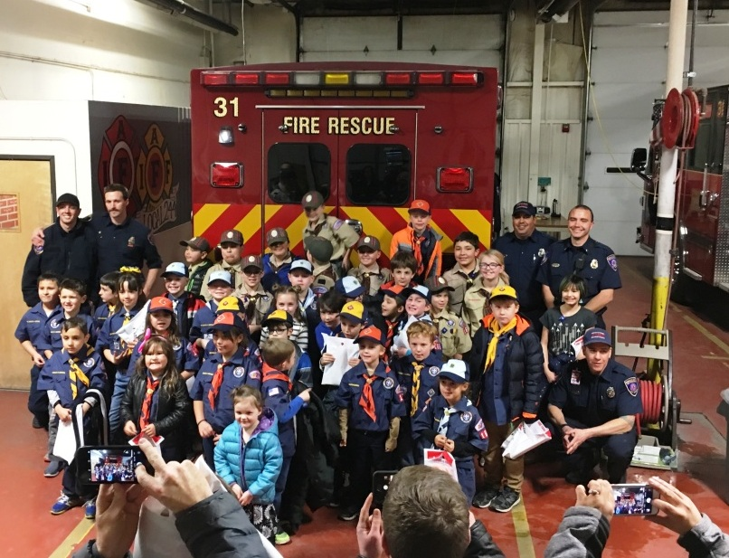A photo of children in front of a fire truck