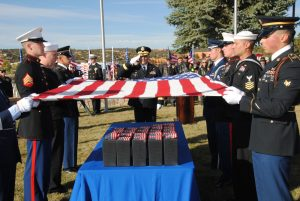 Service members hold a flag over a casket