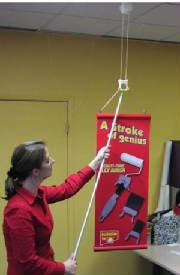 Woman using a tool to hang a banner