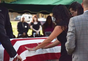 A family gathers around a casket draped with American flag