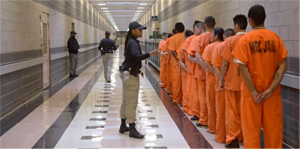 Uniformed woman supervising line of inmates