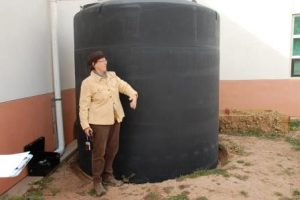 Woman standing next to a large barrel