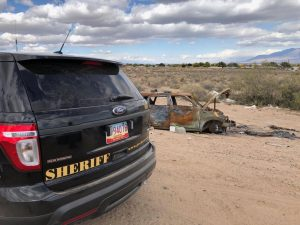 Rear end of Sheriff patrol car with rusty abandoned vehicle in background