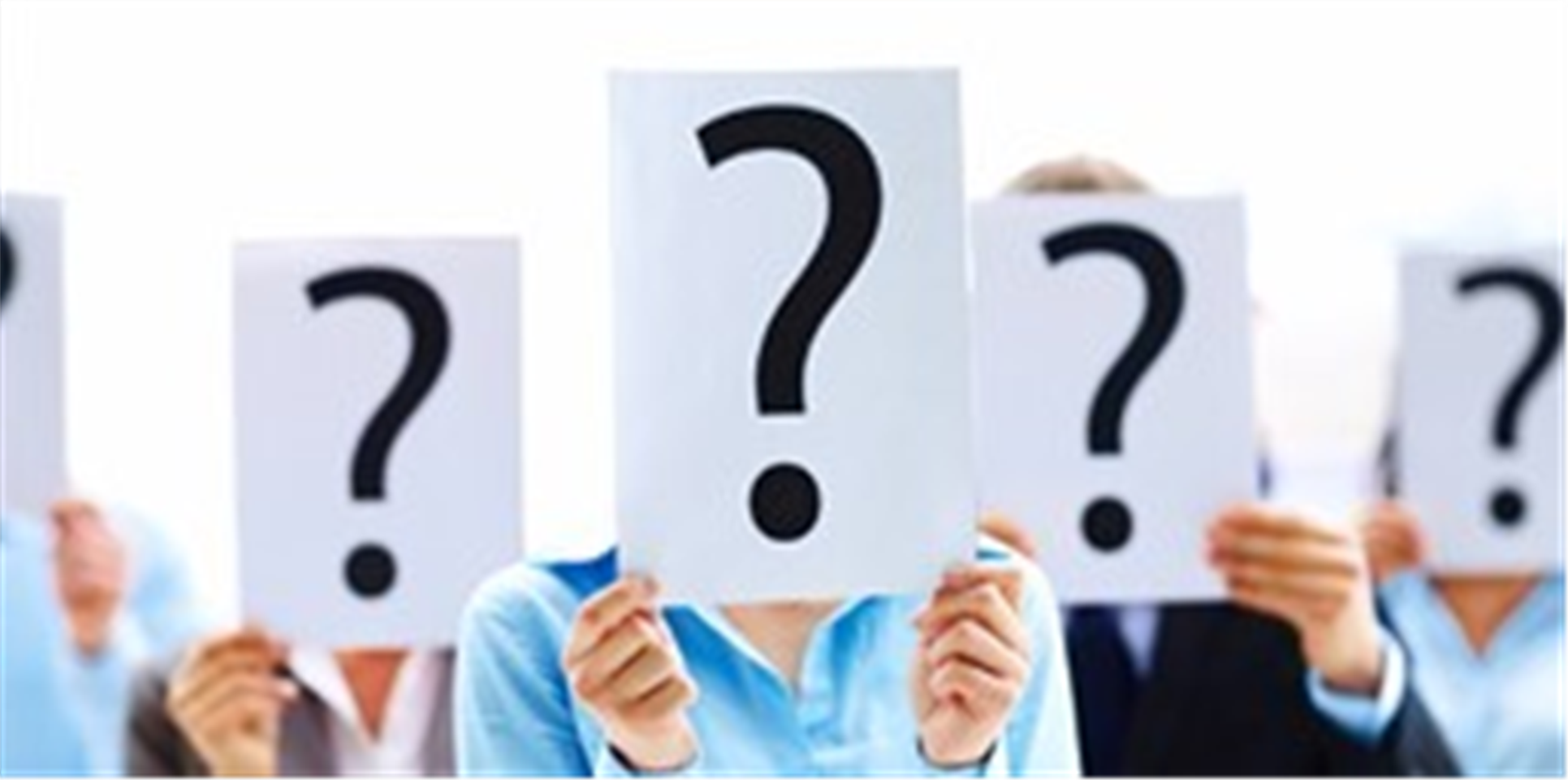 Stock photo of people holding up questions marks