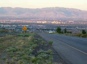 Paved road in foreground with mountains on horizon